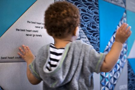 Child in front of fabric wall