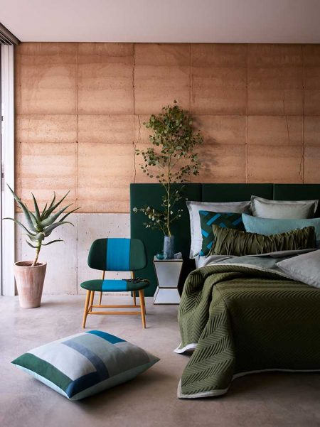 bedroom with teal chair and green bedcover