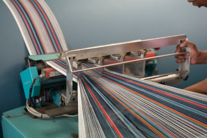 Colorful yarns are woven together, creating sustainably sourced Sunbrella eco friendly upholstery fabric.